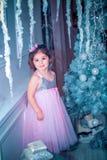 La bambina si è vestita in bello vestito dal fiore bianco di modo che posa vicino all'albero di Natale Immagini Stock Libere da Diritti