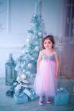 La bambina si è vestita in bello vestito dal fiore bianco di modo che posa vicino all'albero di Natale Immagine Stock