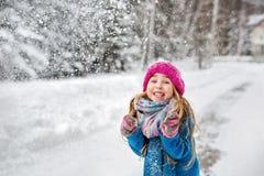La bambina si è vestita in un cappotto blu ed in un cappello rosa che fa smorfie Fotografia Stock