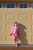 La bambina si leva in piedi la parete vicina Immagine Stock