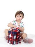 La bambina si siede con tre contenitori di regalo Fotografia Stock