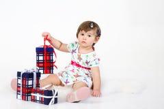 La bambina si siede con tre contenitori di regalo. Fotografia Stock