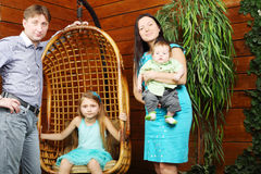 La bambina si siede in sedia e nel padre d'attaccatura, madre con il bambino Fotografia Stock Libera da Diritti