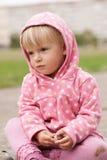 La bambina si siede su terra con un pezzo di gesso Immagini Stock