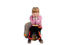 La bambina si siede su un mucchio dei libri Fotografie Stock