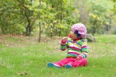 La bambina si siede su un prato e mangia la caramella Fotografia Stock