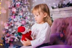 La bambina si siede su un sofà e giudica il giocattolo Santa Claus disponibile Fotografia Stock