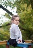 La bambina si siede su un vecchio carosello Fotografia Stock Libera da Diritti