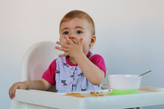 La bambina si siede su una sedia Fotografie Stock