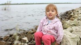 La bambina si siede sulla sponda del fiume archivi video