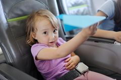 La bambina si siede in una sedia del passeggero dell'aereo fotografie stock libere da diritti