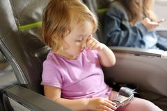 La bambina si siede in una sedia del passeggero dell'aereo fotografia stock libera da diritti