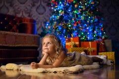 La bambina si trova sul pavimento all'albero e sui sogni del Natale Fotografia Stock Libera da Diritti