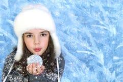 La bambina soffia il fiocco di neve magico sul fondo dell'inverno Fotografia Stock