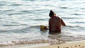 La bambina sola gioca da solo in acqua bassa del mare fotografia stock libera da diritti