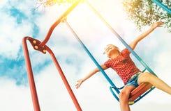 La bambina sorridente felice che oscilla sull'oscillazione largamente ha aperto le armi con il fondo del cielo blu fotografia stock libera da diritti