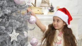 La bambina sorridente felice ha decorato l'albero del nuovo anno archivi video