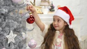 La bambina sorridente felice ha decorato l'albero del nuovo anno video d archivio
