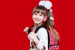 La bambina sorridente sveglia in uniforme scolastico e nel bianco si piega con lo zaino su fondo rosso Fotografia Stock