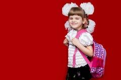 La bambina sorridente sveglia in uniforme scolastico e nel bianco si piega con lo zaino su fondo rosso Immagine Stock Libera da Diritti