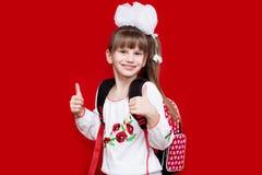 La bambina sorridente sveglia in uniforme scolastico e nel bianco si piega con lo zaino su fondo rosso Fotografie Stock