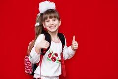 La bambina sorridente sveglia in uniforme scolastico e nel bianco si piega con lo zaino su fondo rosso Immagine Stock