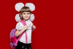 La bambina sorridente sveglia in uniforme scolastico e nel bianco si piega con lo zaino su fondo rosso Di nuovo al banco Fotografia Stock
