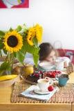 La bambina sta avendo prima colazione a casa Sulla tavola è un mazzo dei fiori dei girasoli e di una torta dolce con frutta, fotografie stock libere da diritti