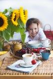 La bambina sta avendo prima colazione a casa Sulla tavola è un mazzo dei fiori dei girasoli e di una torta dolce con frutta, fotografia stock libera da diritti