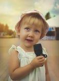 La bambina sta cantando tenendo un microfono Immagine Stock