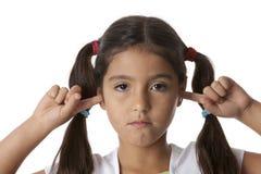 La bambina sta chiudendo le sue orecchie con le sue barrette Fotografie Stock Libere da Diritti