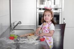 La bambina sta cucinando sulla cucina Divertiresi mentre producendo i dolci ed i biscotti Immagini Stock