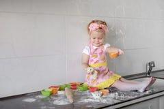 La bambina sta cucinando sulla cucina Divertiresi mentre producendo i dolci ed i biscotti Immagini Stock Libere da Diritti