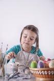 La bambina sta dipingendo le uova immagine stock libera da diritti