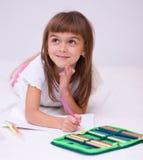La bambina sta disegnando per mezzo delle matite Fotografia Stock