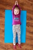 La bambina sta facendo allungando l'esercizio su una stuoia Immagine Stock