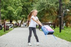 La bambina sta filando con uno zaino sulla via Il concetto di scuola, studio, istruzione, infanzia immagine stock libera da diritti