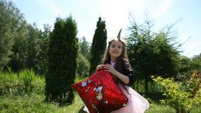 La bambina sta giocando con un cuscino rosso stock footage