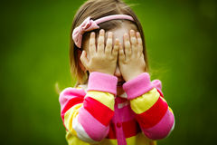 La bambina sta giocando il fronte nascondentesi di pellame-e-ricerca Fotografie Stock