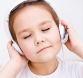 La bambina sta godendo della musica facendo uso delle cuffie Fotografie Stock Libere da Diritti