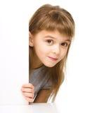 La bambina sta guardando fuori dall'insegna in bianco Immagini Stock Libere da Diritti