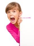 La bambina sta guardando fuori dall'insegna in bianco Immagine Stock Libera da Diritti