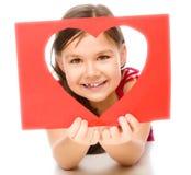 La bambina sta guardando tramite il modello del cuore Immagine Stock Libera da Diritti