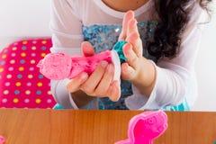 La bambina sta imparando usare la pasta variopinta del gioco Fotografia Stock Libera da Diritti