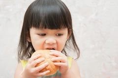 La bambina sta mangiando il pane Fotografia Stock Libera da Diritti