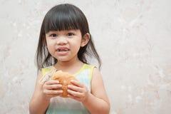La bambina sta mangiando il pane Fotografie Stock Libere da Diritti