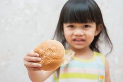 La bambina sta mangiando il pane Immagini Stock
