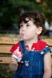 La bambina sta mangiando lo strawber Immagini Stock