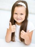 La bambina sta mostrando il pollice sul gesto Immagini Stock