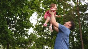 La bambina sta ridendo il volo nell'aria nelle sue armi del papà Felicità di paternità Passeggiata del genitore e del bambino in  stock footage